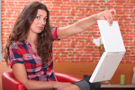 sneer: Woman holding her laptop disdainfully