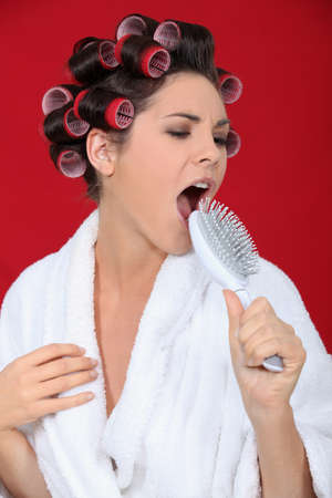 Woman with hair rollers singing into brush photo