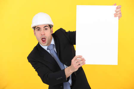stunned: portrait of stunned architect holding board