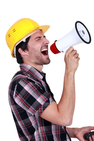 Male construction worker shouting into megaphone Stock Photo