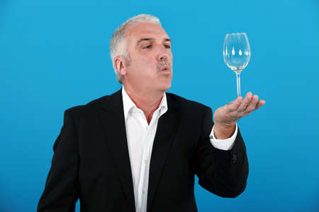 prove: Man blowing a wine glass Stock Photo