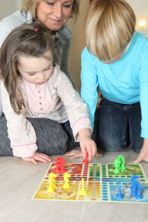 game board: Grandmother watching her grandchildren play a game