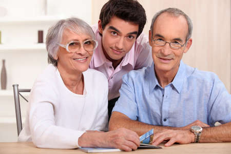 generation gap: Grandson posing with his grandparents Stock Photo