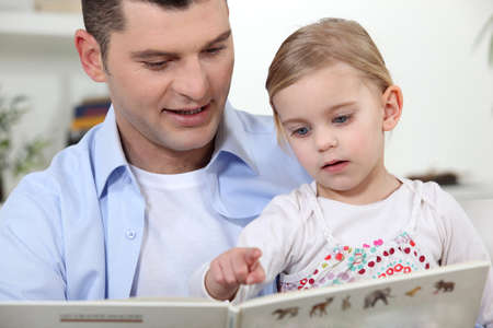 father and his little girl reading a book photo
