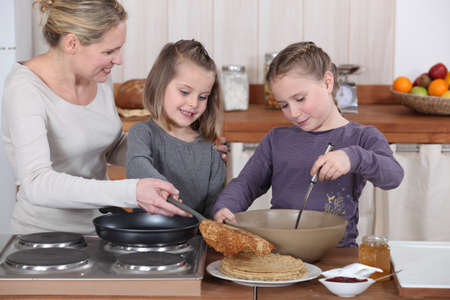 Mother and daughters making pancakes photo