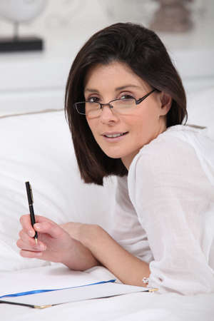 Woman in glasses writing in bed photo