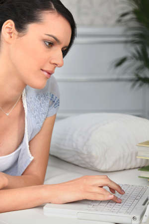 Woman working on her laptop in bed photo