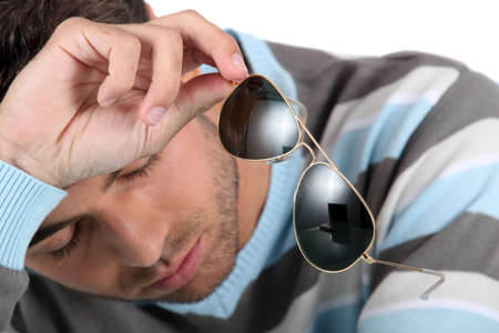 sunstroke: Tired man holding sunglasses Stock Photo