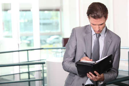 Businessman writing in diary photo