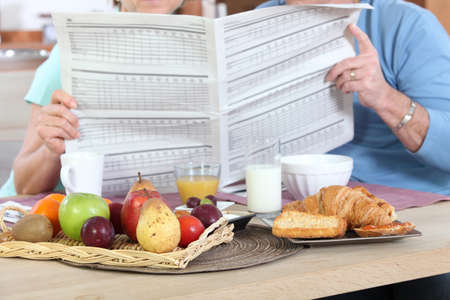 Couple reading newspaper during breakfast photo