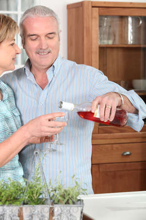 55 years old: Smiling man pouring a glass of rose wine for his lovely wife Stock Photo
