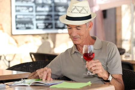 senior on vacation drinking fresh wine in a restaurant photo