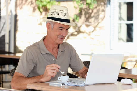 hombre tomando cafe: Hombre de pelo gris de tomar caf� en la terraza con ordenador port�til