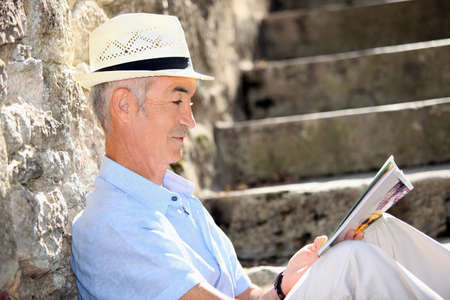 60 64 years: Senior man reading a magazine on some old stone steps Stock Photo