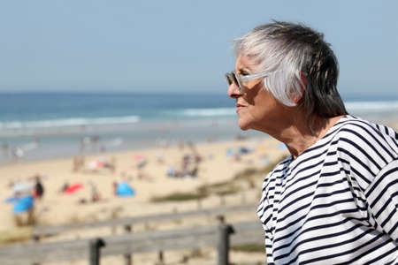 60 64 years: Senior woman looking out over a sandy beach on a summer day