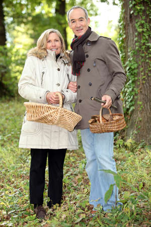 55 to 60: Couple collecting wild mushrooms Stock Photo