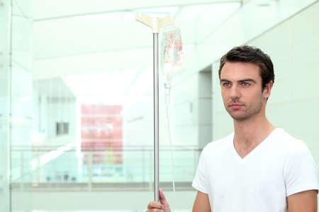 malignancy: Man stood with IV drip