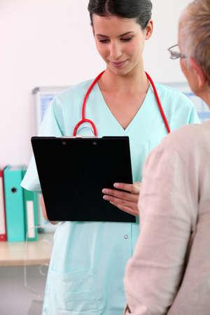 nurse assisting senior patient photo