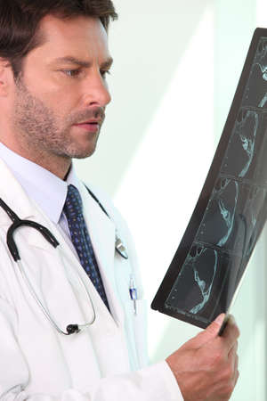Male doctor stood holding and examining x ray Stock Photo - 11135379