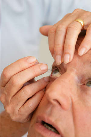 Woman helping man put in contact lenses photo