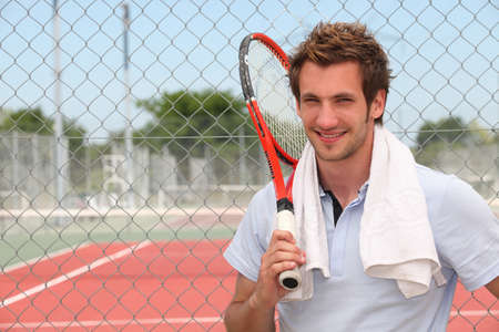 Een tennisser poseren voor een tennisbaan met zijn racket. Stockfoto