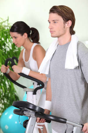 Young couple using gym equipment Stock Photo - 11135016