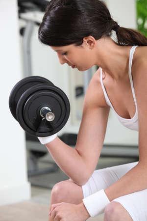 toning: Woman lifting a dumbbell Stock Photo