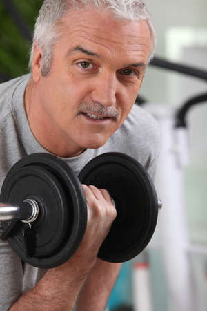 50 55: Man lifting a dumbbell at the gym