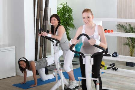 Young women using gym equipment photo