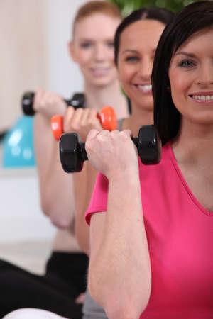 levantando pesas: Mujer levantando pesas en el gimnasio Foto de archivo