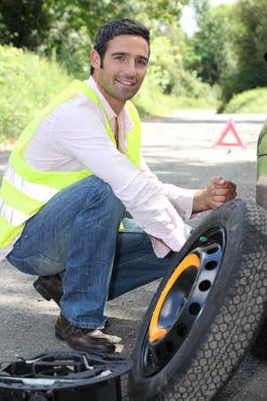 man changing a wheel photo