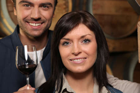 Couple drinking red wine in a cellar photo