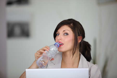 beauteous: portrait of classy brunette working on laptop with bottle of water