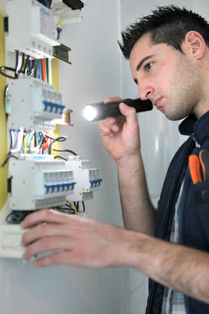 Electrician examining fuse box photo