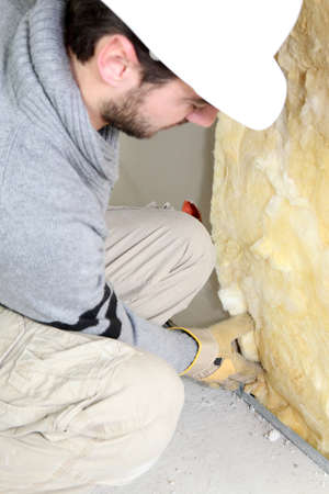rock wool: Wall insulation being installed by builder Stock Photo