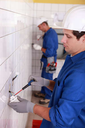 Pair of electricians wiring a white tiled room photo