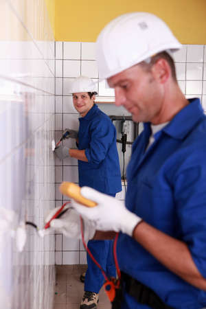 Electricians working in a tiled room Stock Photo - 11338830