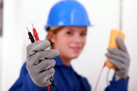 A female electrician holding a voltmeter. photo