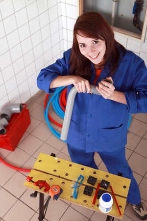 tradesperson: Female plumber with grey plastic pipe and tools