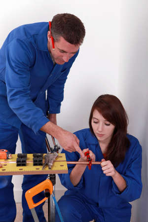 jumpsuit: Experienced workman showing an apprentice how to use a pipe wrench Stock Photo
