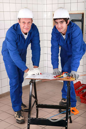 hábil: two skilled tradesman in blue jumpsuites watching a drawing