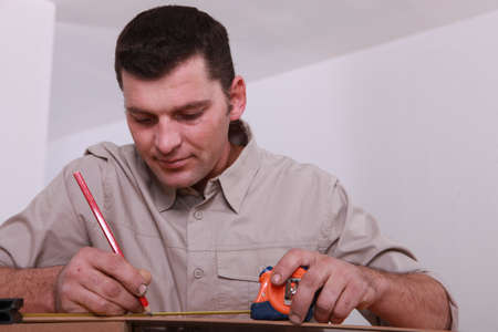 Tradesman marking a measurement with a pencil Stock Photo - 11338781