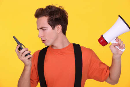 Confused man with a loudspeaker and walky-talky Stock Photo - 11338872