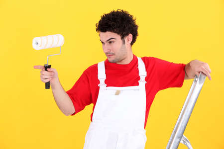 redecorating: Man with paint roller and ladder
