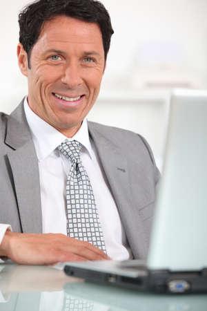 sensational: Satisfied businessman in front of laptop computer