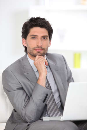 Handsome executive using a laptop computer Stock Photo - 11342041
