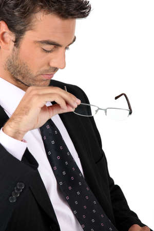 Businessman taking off his glasses photo