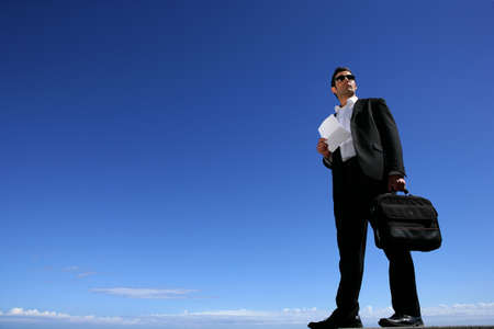 Confident businessman in front of blue sky Stock Photo - 11338829