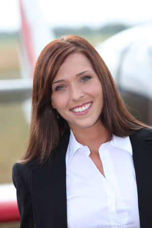 stewardess: Smiling hostess in front of an airplane