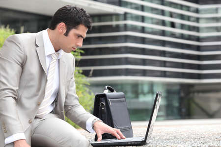 Man using a laptop outside photo